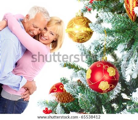 Elderly  happy couple near a Christmas tree. Isolated over white background - stock photo