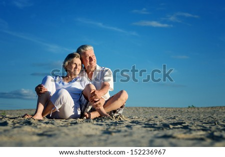Elderly happy couple relaxing in the sand together