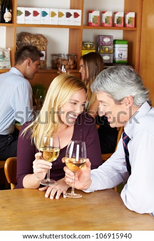 Elderly happy couple sitting with glass of white wine in a caf�© - stock photo