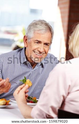 Elderly happy man talking to woman in a restaurant - stock photo