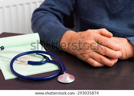 Elderly health insurance concept - close-up of the wrinkled hands of an old man . - stock photo