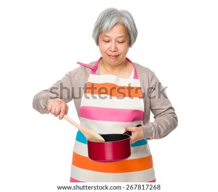 Elderly housewife use of saucepan - stock photo