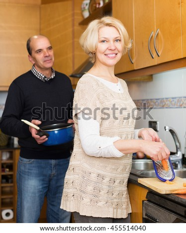 Elderly husband helping happy wife to cook in kitchen