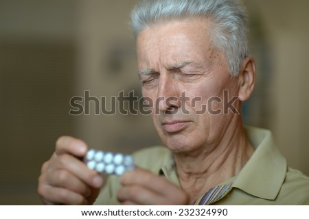 Elderly ill man with pills in hand - stock photo