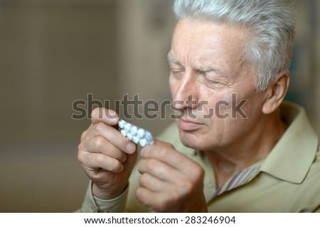 elderly ill man with pills in hand - stock photo