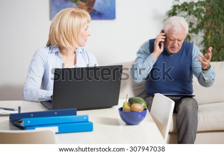 Elderly irate man talking phone with the client - stock photo
