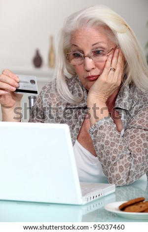 Elderly lady confused by prospect of shopping on line - stock photo
