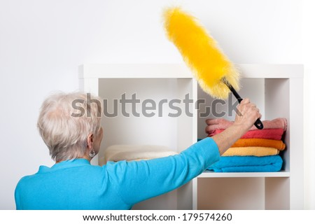 Elderly lady during dusting furniture at home - stock photo