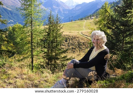 Elderly lady enjoying a vacation in the Swiss Alps sitting on a rock in a scenic valley in the canton of Valais smiling at the camera. - stock photo