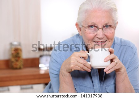 Elderly lady enjoying cup of tea in her kitchen - stock photo