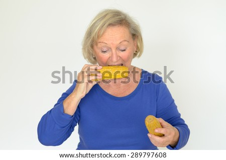 Elderly lady enjoying fresh corn on the cob biting into the kernels with a happy smile in a healthy diet concept, over grey
