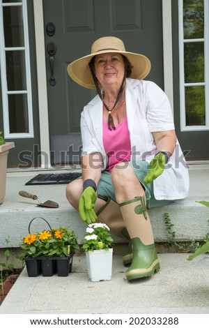 Elderly lady getting ready to transplant flower seedlings sitting on the steps of her porch in a sunhat, gumboots and gloves with the plants in front of her - stock photo