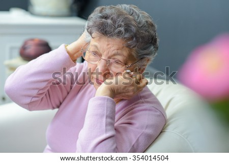 Elderly lady holding her head in her hands - stock photo