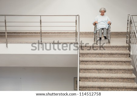 Elderly lady in wheelchair at top of stairs in hospital - stock photo