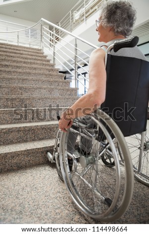 Elderly lady in wheelchair looking up hospital stairs - stock photo