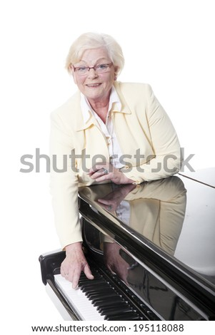 elderly lady in yellow at the piano in studio with white background