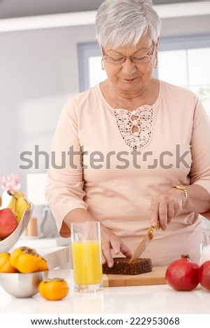 Elderly lady making healthy food, slicing brown bread. - stock photo