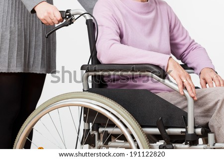 Elderly lady on wheelchair and her guardian - stock photo
