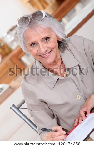 Elderly lady paying bills - stock photo