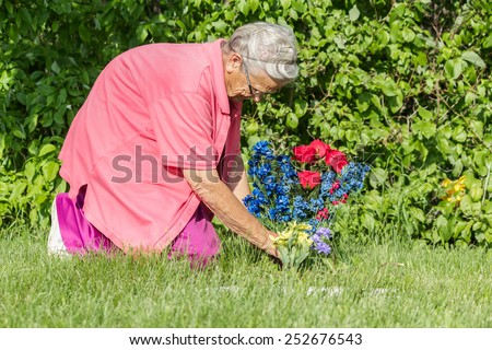 elderly lady placing flowers on a grave