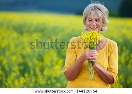 elderly lady plucking flowers on a field - stock photo