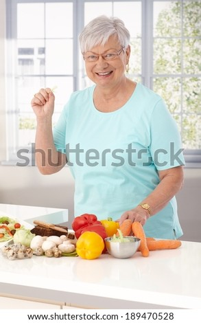 Elderly lady preparing healthy food in kitchen, using vegetables and brown bread. - stock photo