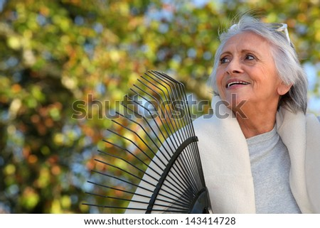 Elderly lady raking leaves in her garden - stock photo