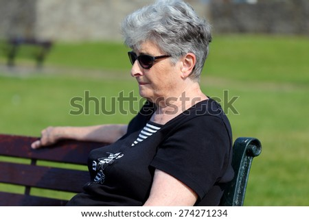 Elderly lady relaxes on a bench - copy space  - stock photo