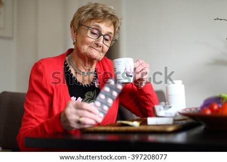 elderly lady staring in amazement at the pills she has to take/ medication/ elderly lady staring at her medication
