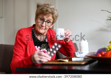 elderly lady staring in amazement at the pills she has to take/ medication/ elderly lady staring at her medication - stock photo