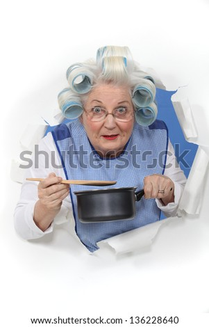 Elderly lady stirring sauce pan