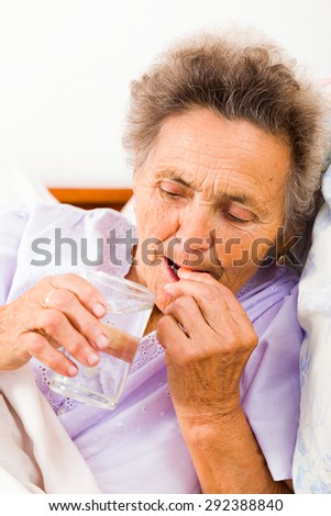 Elderly lady taking pills with glass of water at home. - stock photo