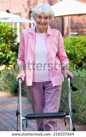 Elderly lady using a walker in the garden standing on a pathway with buildings in the background smiling at the camera - stock photo