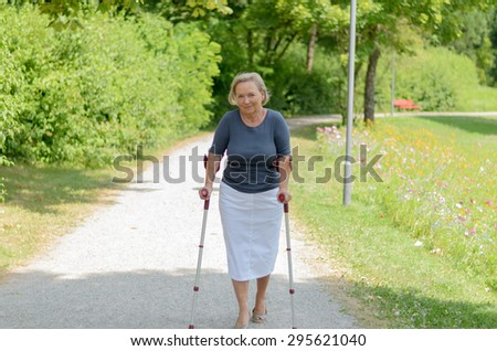 Elderly lady walking in the country along a rural lane on crutches as she tries to exercise and stay fit despite a handicap or injury - stock photo