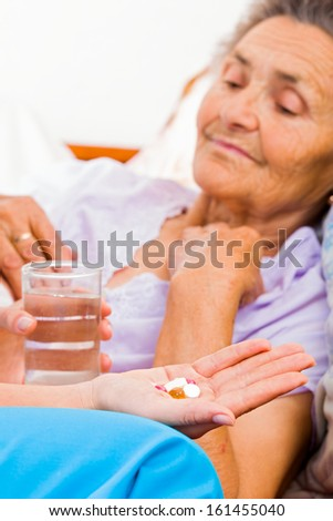 Elderly lady with Alzheimer's disease taking pills. - stock photo