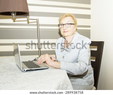 Elderly lady with notebook (laptop) computer. - stock photo