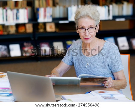Elderly lady working with laptop - stock photo