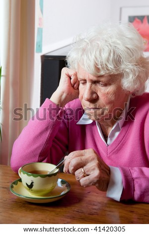 Elderly lonely woman depressed sitting at the table - stock photo