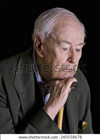 elderly, looking down, leaning on his cane - stock photo