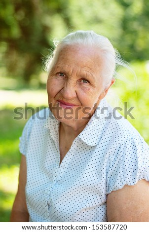 Elderly lovely woman sitting in a park, sunny summer day - stock photo