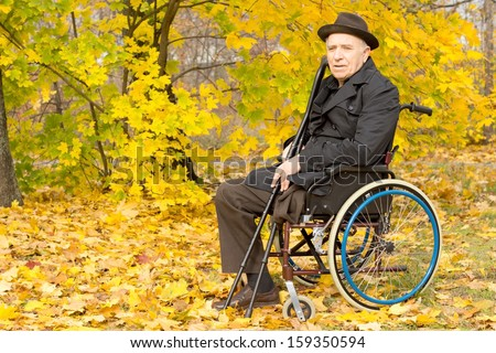 Elderly male amputee confined to a wheelchair sitting holding his crutches enjoying a day in a colourful yellow autumn or fall park, with copyspace - stock photo