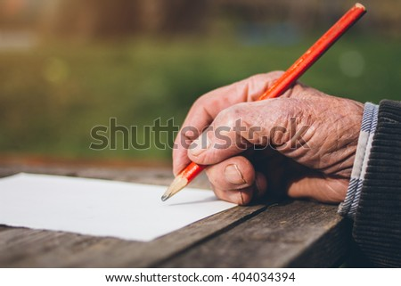 Elderly male hands on wooden table . writing on letter - stock photo
