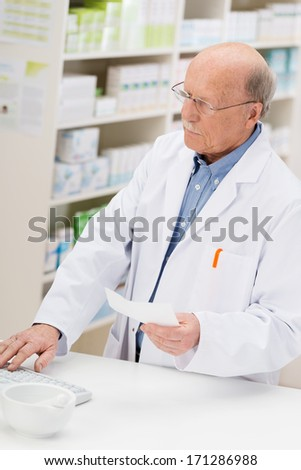 Elderly male pharmacist entering prescription details onto a computer before dispensing the tablets - stock photo