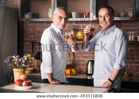 Elderly man and his son drinking in the kitchen