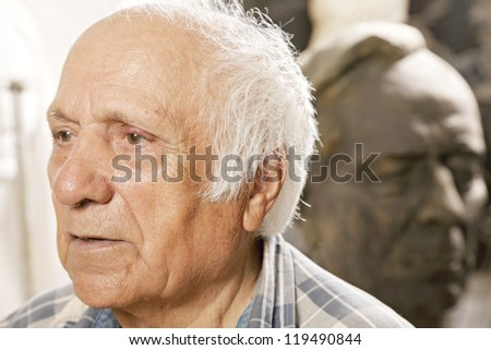 Elderly man and statue head and shoulders portrait - stock photo