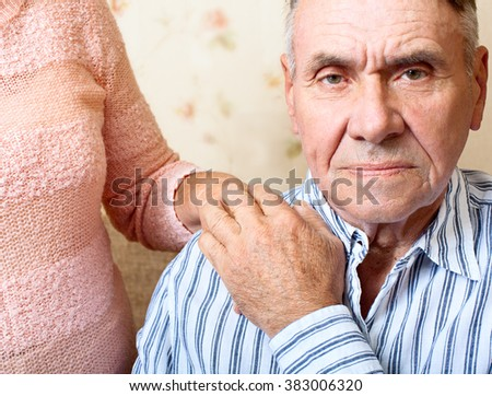 Elderly man and woman sitting close together on sofa in their living room and looking at the camera close up - stock photo