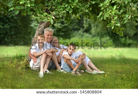 elderly man and woman with their grandchildren resting under a tree