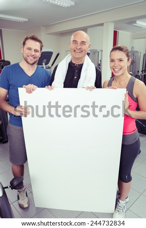 Elderly man and young couple holding a blank white sign with copyspace for your text smiling happily at the camera in their sportswear as they pose together at the gym - stock photo