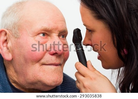 Elderly man at the optician's for vision test. - stock photo