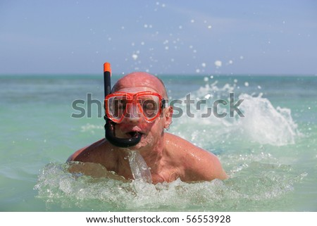 Elderly man bathing in the sea with mask and snorkel